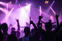 Le siluette del concerto ammucchiano davanti alle luci luminose della fase Fotografia Stock Libera da Diritti