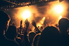 Le siluette del concerto ammucchiano davanti alle luci luminose della fase Immagine Stock
