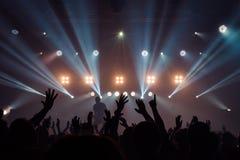 Le siluette del concerto ammucchiano davanti alle luci luminose della fase Immagine Stock Libera da Diritti