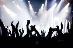 Le siluette del concerto ammucchiano davanti alle luci luminose della fase immagini stock libere da diritti