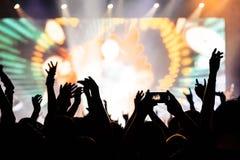 Le siluette del concerto ammucchiano davanti alle luci luminose della fase Immagini Stock