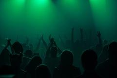 Le siluette del concerto ammucchiano davanti alle luci luminose della fase Fotografie Stock