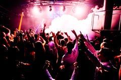 Le siluette del concerto ammucchiano davanti alle luci luminose della fase con i coriandoli Immagine Stock Libera da Diritti