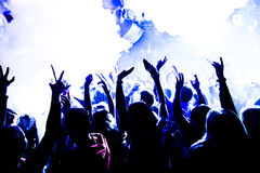 Le siluette del concerto ammucchiano davanti alle luci luminose della fase con i coriandoli fotografia stock libera da diritti