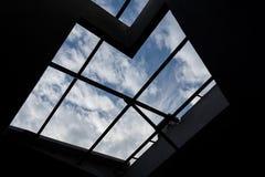 Le siluette del fascio di tetto cercano nel cielo blu Fotografia Stock