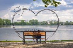 Le siluette del ragazzino e della ragazza stanno sedendo su un banco dentro per fotografia stock libera da diritti