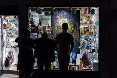 Le siluette della gente guardano la pittura al negozio a Venezia Immagine Stock