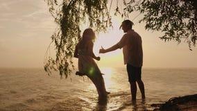Le siluette di giovane coppia, un uomo sta rotolando la sua moglie su un'oscillazione Contro lo sfondo del mare al tramonto ` s stock footage
