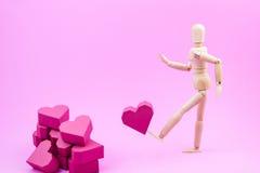 Le simulacre en bois donnent un coup de pied la forme rouge de coeur de boîte de papier à une pile de Photo libre de droits
