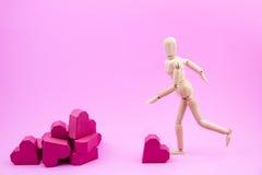 Le simulacre en bois donnent un coup de pied la forme rouge de coeur de boîte de papier à une pile de Photo stock