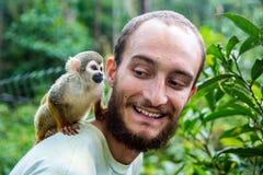 Le singe de doigt de singe de poche aka saute à cloche-pied sur le dos du ` s de l'homme Image stock