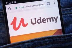 Le site Web d'Udemy montré sur le smartphone caché dans des jeans empochent images libres de droits