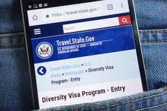 Le site Web de Département d'État des USA au sujet du programme de visa de diversité montré sur le smartphone caché dans des jean photo stock