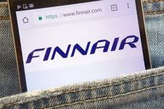 Le site Web de Finnair montré sur le smartphone caché dans des jeans empochent photographie stock