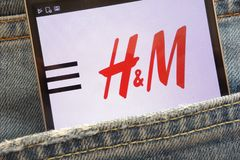 Le site Web de H&M montré sur le smartphone caché dans des jeans empochent photo stock
