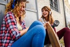 Le skateboarding flickor som sitter i gatan som ut hänger Royaltyfri Bild