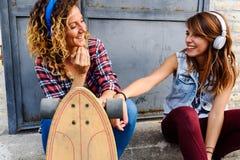 Le skateboarding flickor som sitter i gatan som ut hänger Royaltyfria Bilder