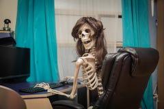 le skelettet i ett peruksammanträde i rum på svart läderstol bak skrivbordet Royaltyfri Foto