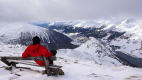 Le skieur de Backcountry fait une pause et s'assied sur un banc de sommet et apprécie la vue de Davos en hiver image libre de droits