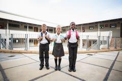 Le skolaungar som står i skolaterrass fotografering för bildbyråer