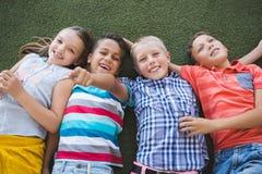 Le skolbarn som ligger på gräs i universitetsområde Royaltyfria Bilder