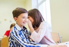 Le skolflickan som viskar till klasskompisörat Royaltyfri Bild