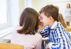 Le skolflickan som viskar till klasskompisörat Royaltyfri Fotografi