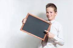 Le skolpojken med den svart tavlan för rengöringsvart Fotografering för Bildbyråer