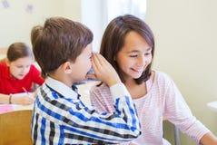 Le skolpojken som viskar till klasskompisörat Royaltyfri Foto
