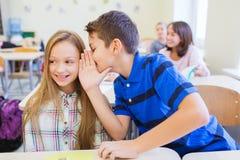 Le skolpojken som viskar till klasskompisörat Arkivfoton