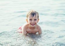 le skratta vit den unga pysen för Caucasian i vattenhavhavet arkivbilder