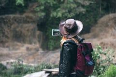 Le smartphone de touristes femelle d'utilisation, prennent une photo avec le chapeau de sac à dos et de cowboy regarder la rivièr images libres de droits
