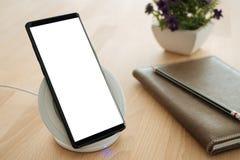 Le smartphone mobile est placé sur un chargeur rapide sans fil Images stock
