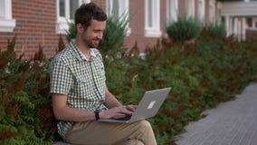 Le smartwatch de port habillé occasionnel d'homme se reposent sur la vidéo de banc causant par l'ordinateur portable banque de vidéos