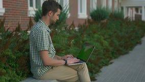 Le smartwatch de port indépendant habillé occasionnel d'homme se reposent sur le banc et utilisent l'ordinateur portable banque de vidéos