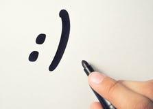 Le smilie est dessiné sur un morceau de papier Image stock
