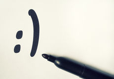Le smilie est dessiné sur un morceau de papier Photos stock