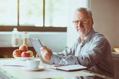 Le smilign positif a vieilli l'homme s'asseyant dans la cuisine Images libres de droits