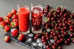 Le smoothie et le Detox frais de fraise arrosent avec des cerises en deux verres sur un fond gris Boissons saines de detox Photos stock