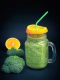 Le smoothie orange de céleri de brocoli de légume fruit de fruit frais, secouent le fond foncé Image libre de droits