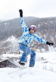 Le snowboarder heureux saute sur le snowboard et les srceams photos stock