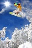 Le Snowboarder sautant contre le ciel bleu photos stock
