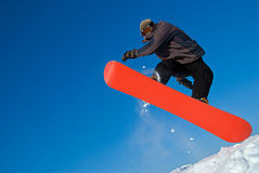 Le Snowboarder sautent en air, vol de neige Photo stock