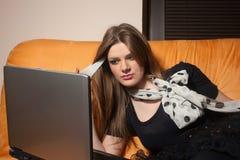 le sofa för flickabärbar dator Fotografering för Bildbyråer