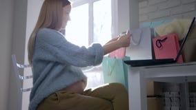 Le soin du futur enfant, fille de maternité heureuse avec le ventre nu examine l'Internet de vêtements achetant pour futur se rep banque de vidéos