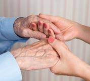 Le soin est à la maison des personnes âgées Photo stock