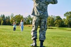 Le soldat arrière de vue rencontre sa famille dehors Photo stock