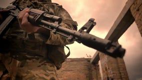Le soldat authentique fort se tient avec confiance et tient l'arme à feu automatique, bâtiment extérieur et détruit, l'espace vid clips vidéos