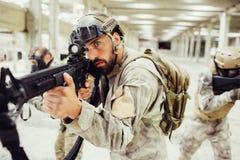 Le soldat courageux et sérieux se tient avec ses combads dans longue une salle lumineuse et brillante Le type barbu prend le but  photographie stock libre de droits