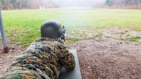 Le soldat dans le d?partement militaire, avec un casque sur sa t?te, se trouve au sol et vise la cible images stock